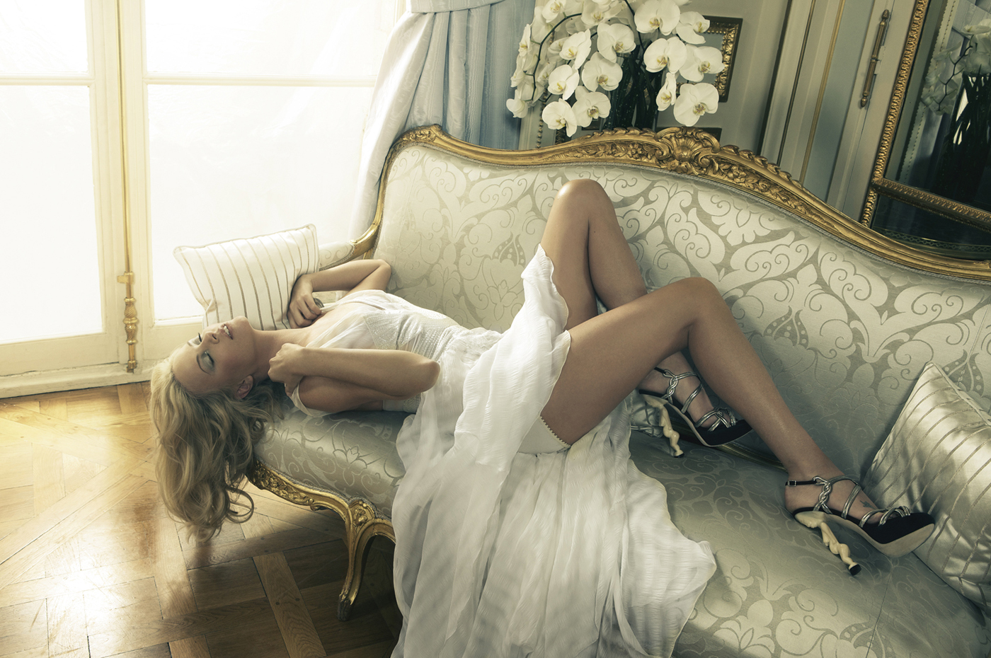 Charlize Theron photoshoot wearing a white gown, lying on a sofa