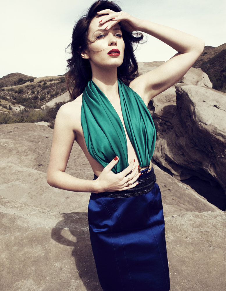 Emily Blunt wearing a green top and blue skirt in a desert photoshoot