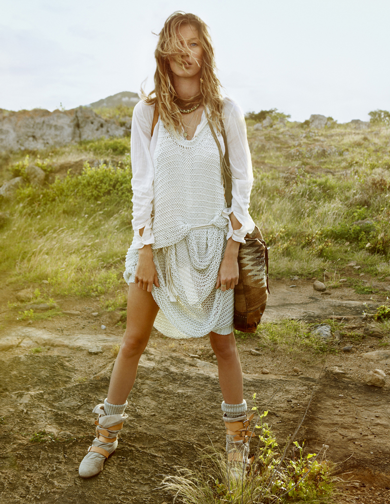 Gisele Bundchen wearing a white dress and ankle boots