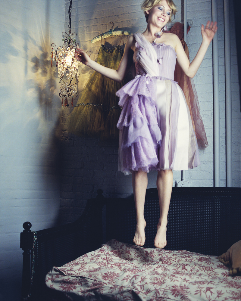 Michelle Williams wearing a purple dress, jumping on a bed