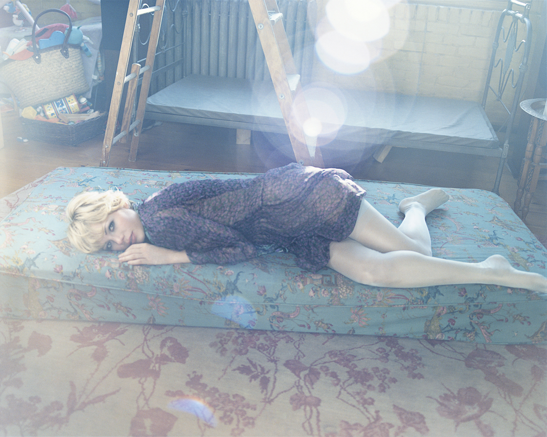 Michelle Williams wearing a long-sleeved black dress, lying down on a mattress