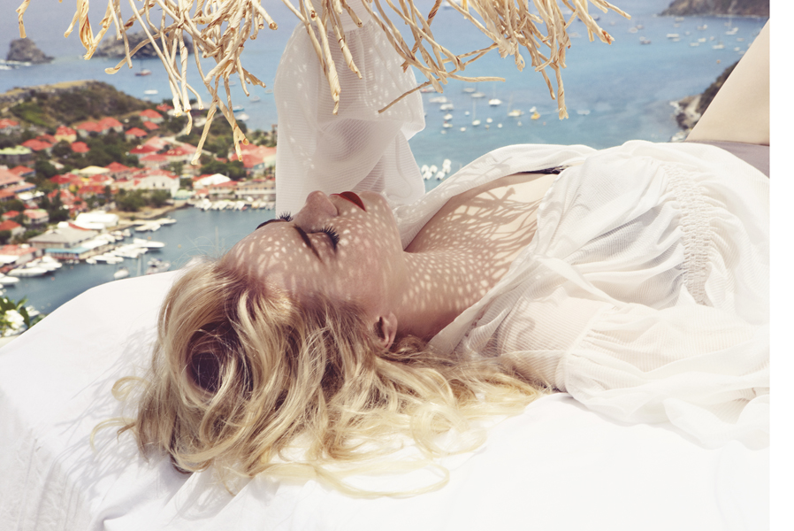 Emma Stone lying down on the beachside, wearing a white top