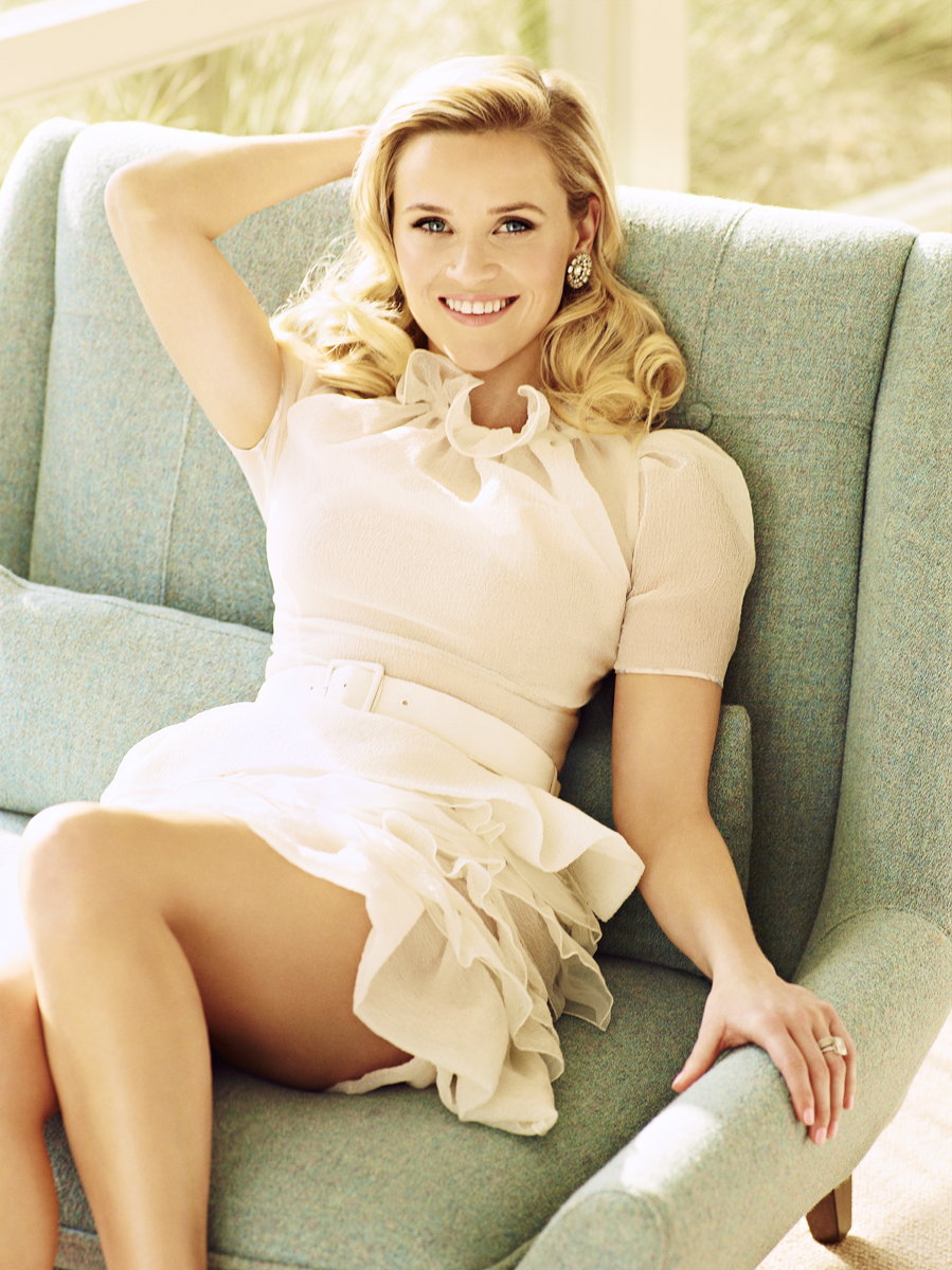 Reese Witherspoon wearing a white dress, sitting on a green sofa