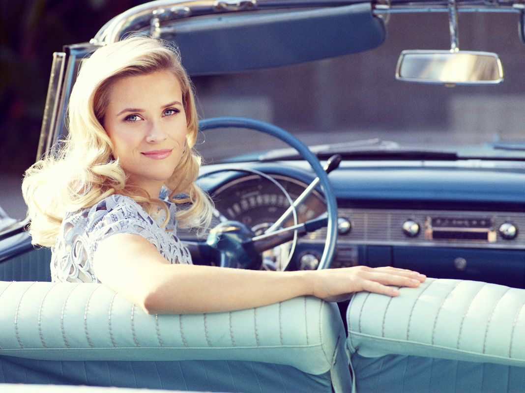 Reese Witherspoon wearing a blue lace dress in a vintage car