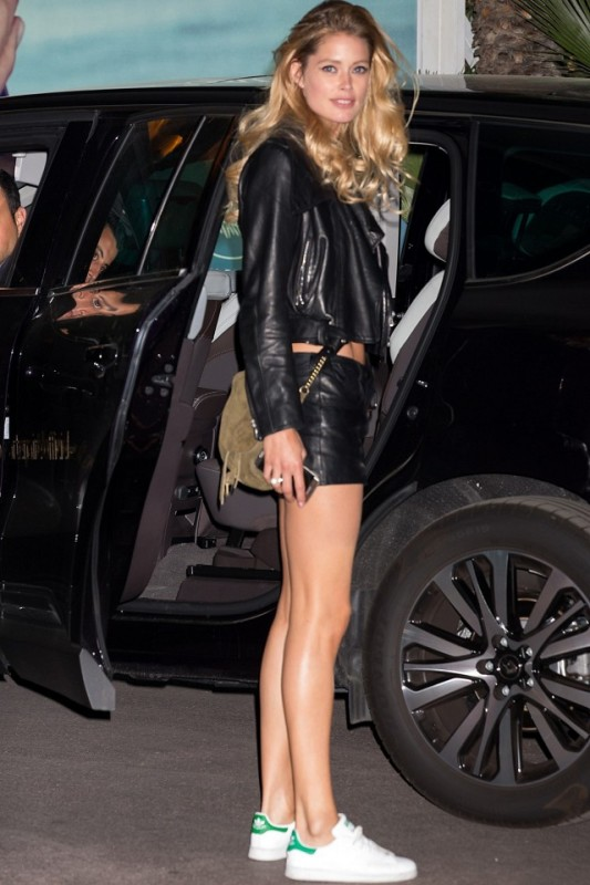 Doutzen Kroes in a black leather jacket, black leather shorts, and white sneakers