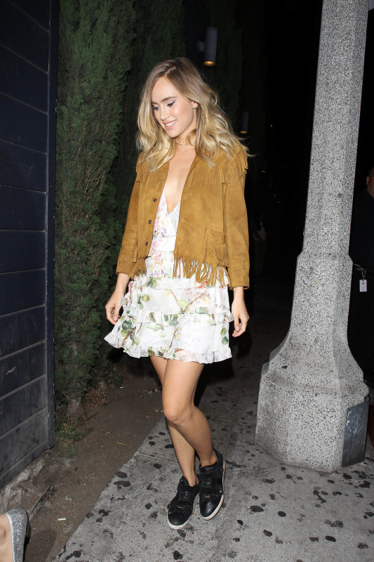 Suki Waterhouse wearing a suede fringed jacket, floral layerd dress, and black sneakers
