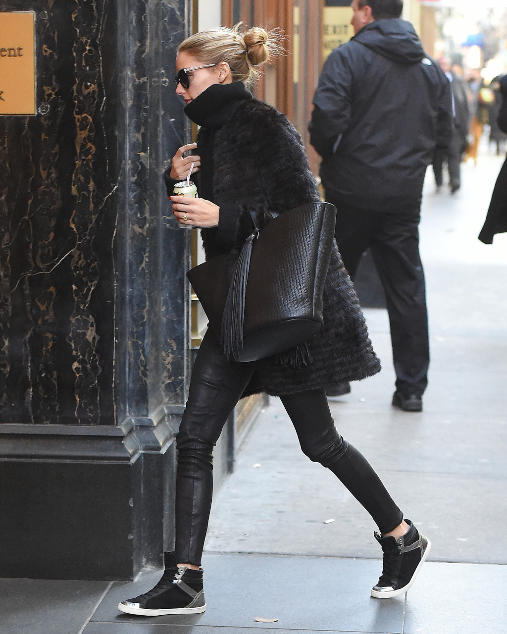 Olivia Palermo in a black turtleneck top shaggy coat and black leggings