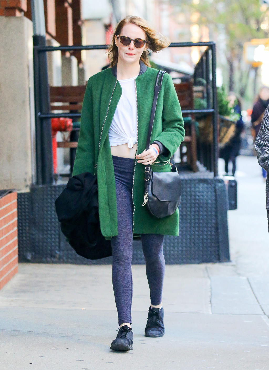Emma Stone in a green coat and gray leggings