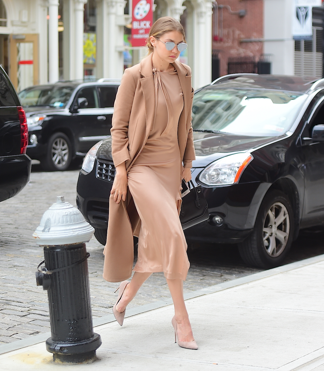 Gigi Hadid struts her model physique in tan fringed dress.
