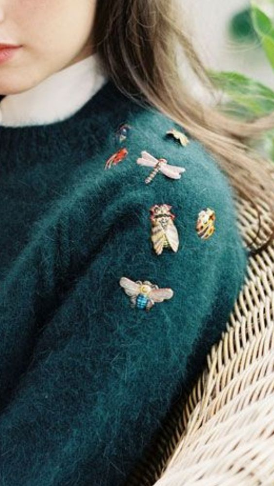 green jumper with brooches
