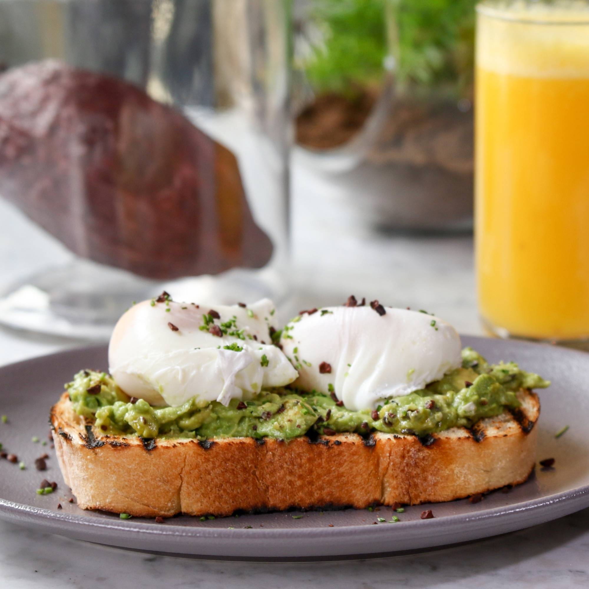 poached eggs with crushed avocado on sourdough bread