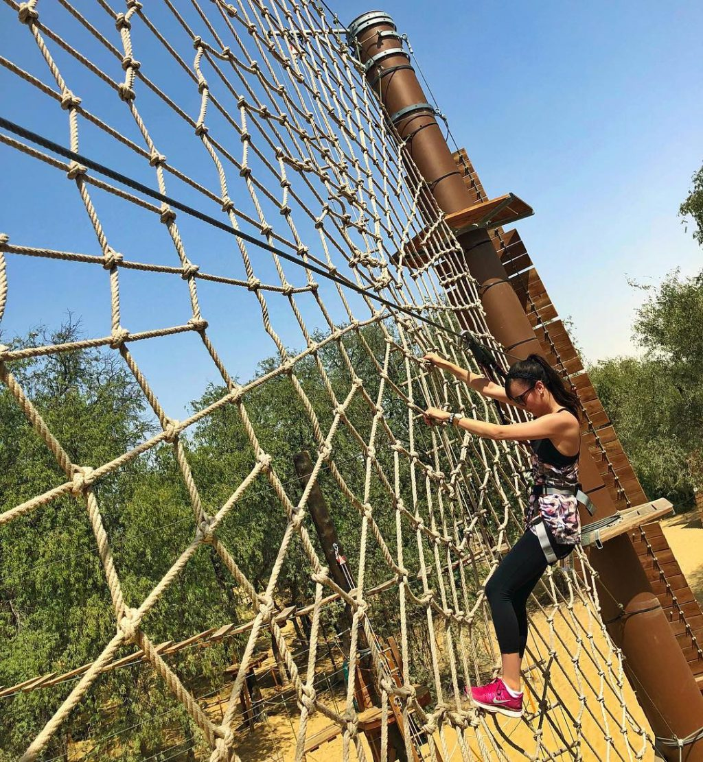 woman climbing obstacle course