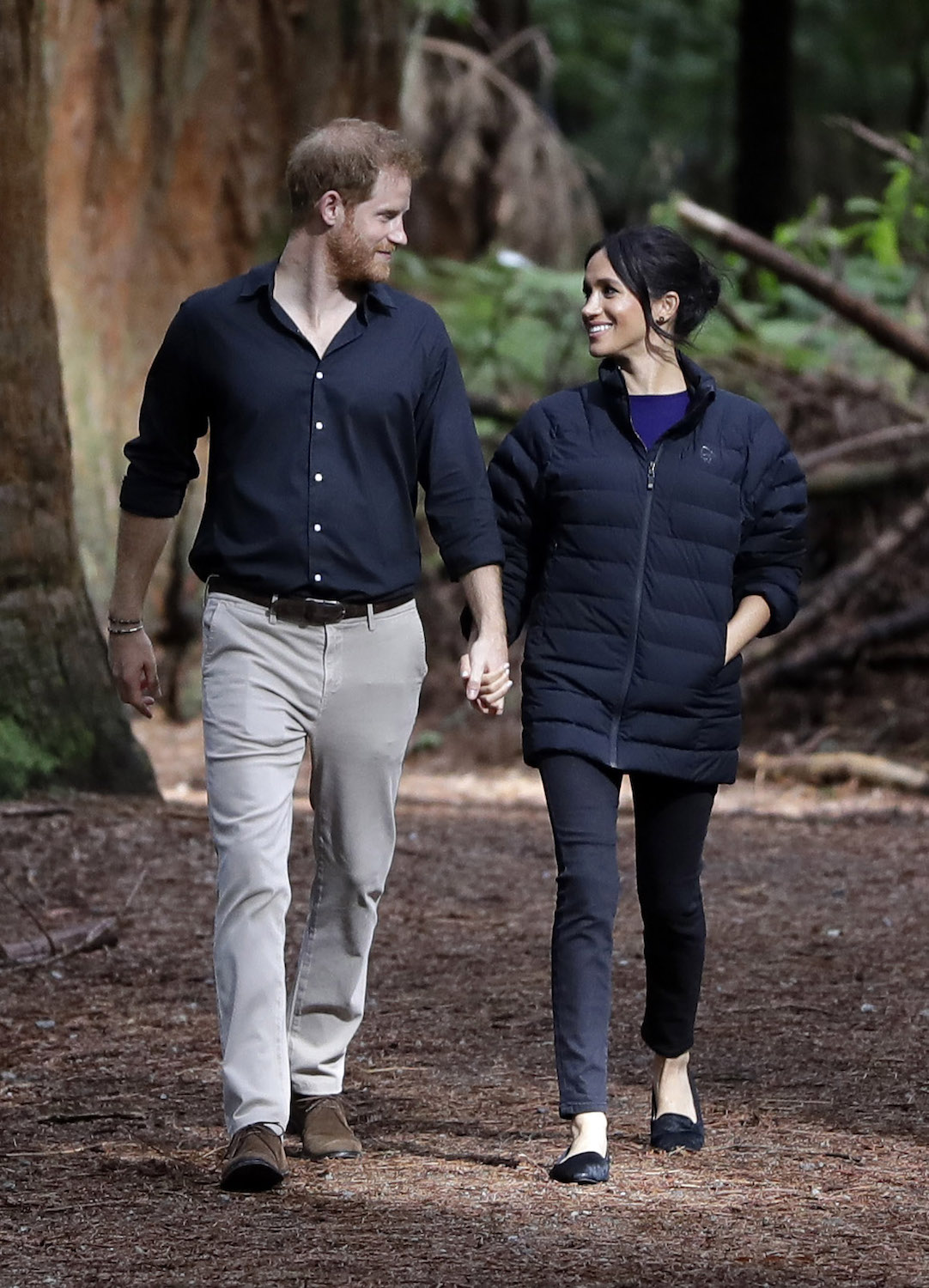 Britain's Prince Harry and Meghan, Duchess of Sussex walk through a Redwoods forest in Rotorua, New Zealand, Wednesday, Oct. 31, 2018. Prince Harry and his wife Meghan are on the final day of their 16-day tour of Australia, New Zealand and the South Pacific. (AP Photo/Kirsty Wigglesworth,Pool)
