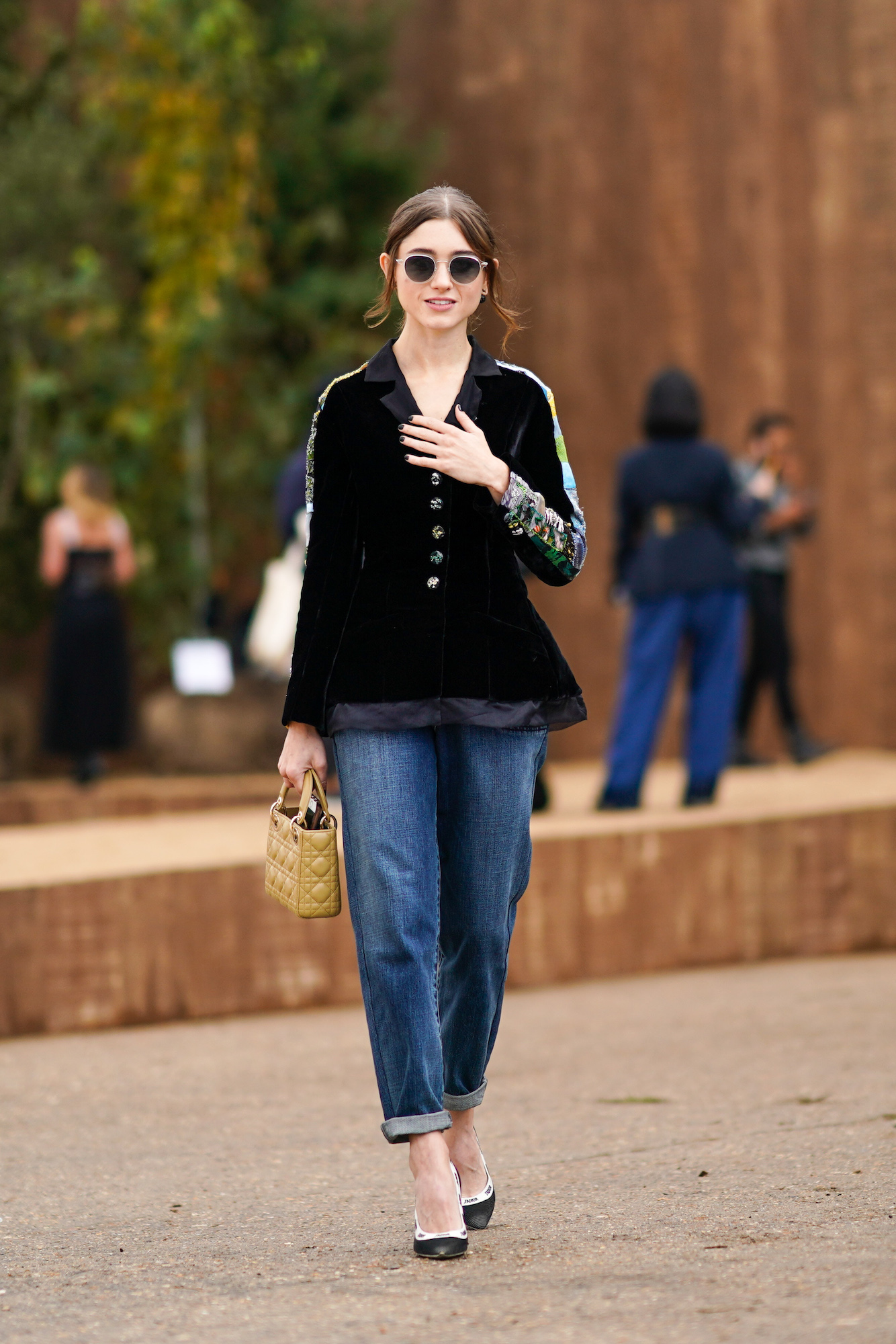 "PARIS, FRANCE - SEPTEMBER 24: Actress Natalia Dyer who portrays the character ""Nancy Wheeler"" in the Netflix series ""Stranger Things"", wears sunglasses, a black top with printed colored sleeves, a yellow Lady Dior quilted bag, blue denim cropped jeans, pointy shoes, outside Dior, during Paris Fashion Week - Womenswear Spring Summer 2020, on September 24, 2019 in Paris, France. (Photo by Edward Berthelot/Getty Images)"